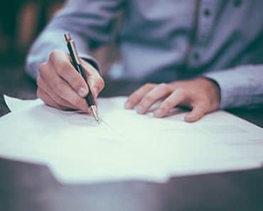 carta de apresentação - homem assinando a carta - Foto por Scott Graham