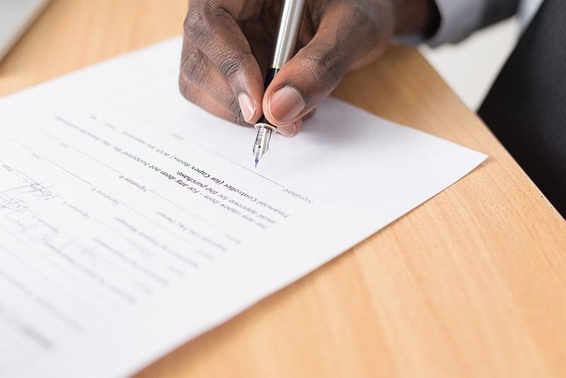 carta de apresentação - homem assinando a carta - Foto por Cytonn Photography