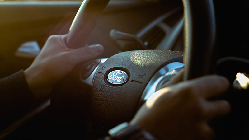 Jovem aprendiz ford - homem segurando um volante da ford - Foto por Jeremy Chen